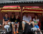 Family riding rickshaws in the Beijing Hutongs