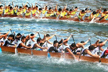 Chinese Dragon Boat Festival - Teams of rowers paddle together in unison as they race to the finish line