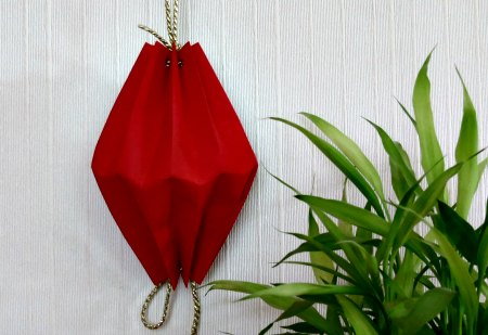 Make this Chinese Paper Lantern, a little paper, some tape, hole puncher, some string, and a little folding.